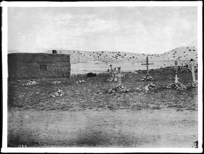 Photograph of a grouping of five penitente crosses stuck in small piles of stones, San Rafael, New Mexico, ca.1900. Via Wikimedia Commons.