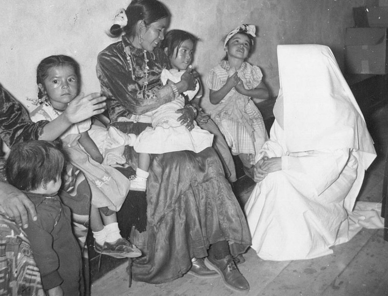 A Hospital Sister telling a story to Navajo children after Mass.