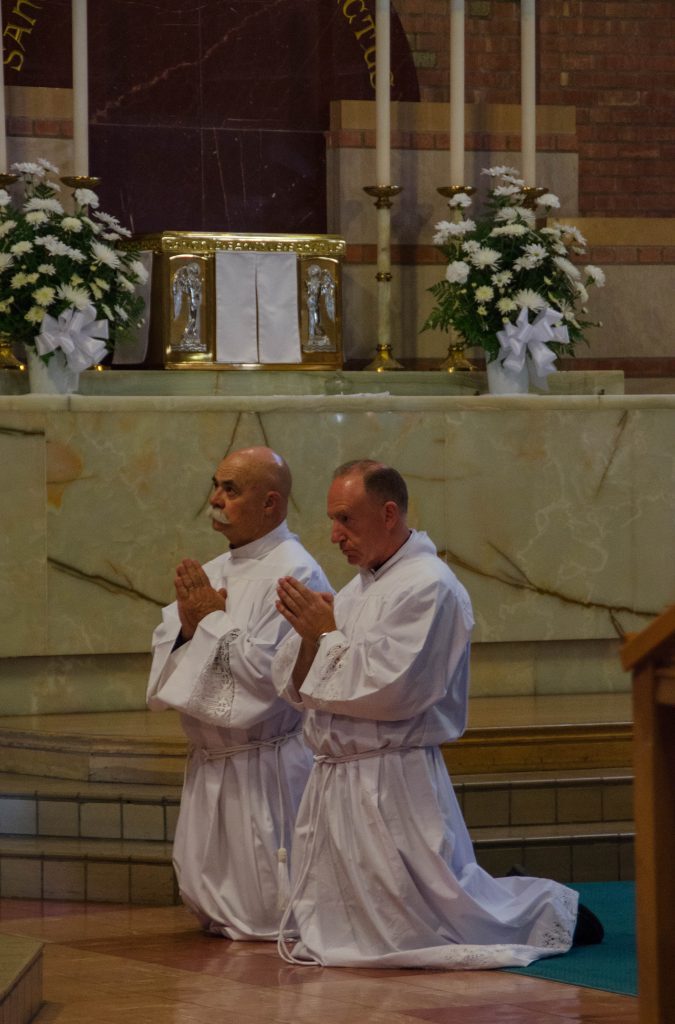 Ed Schaub, left, and John Cormack, right, kneel during their ordination.
