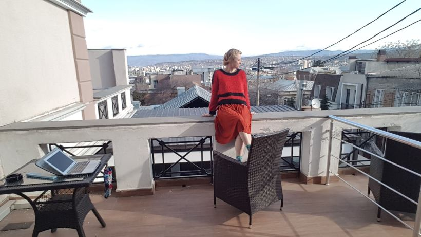 Podcast host Holly on terrace overlooking Tbilisi city scape