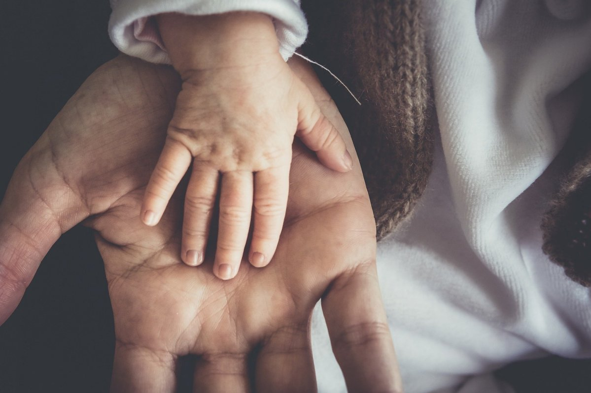 Child's hand on father's hands