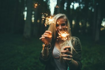 Sparklers: Woman holds sparklers  with intention