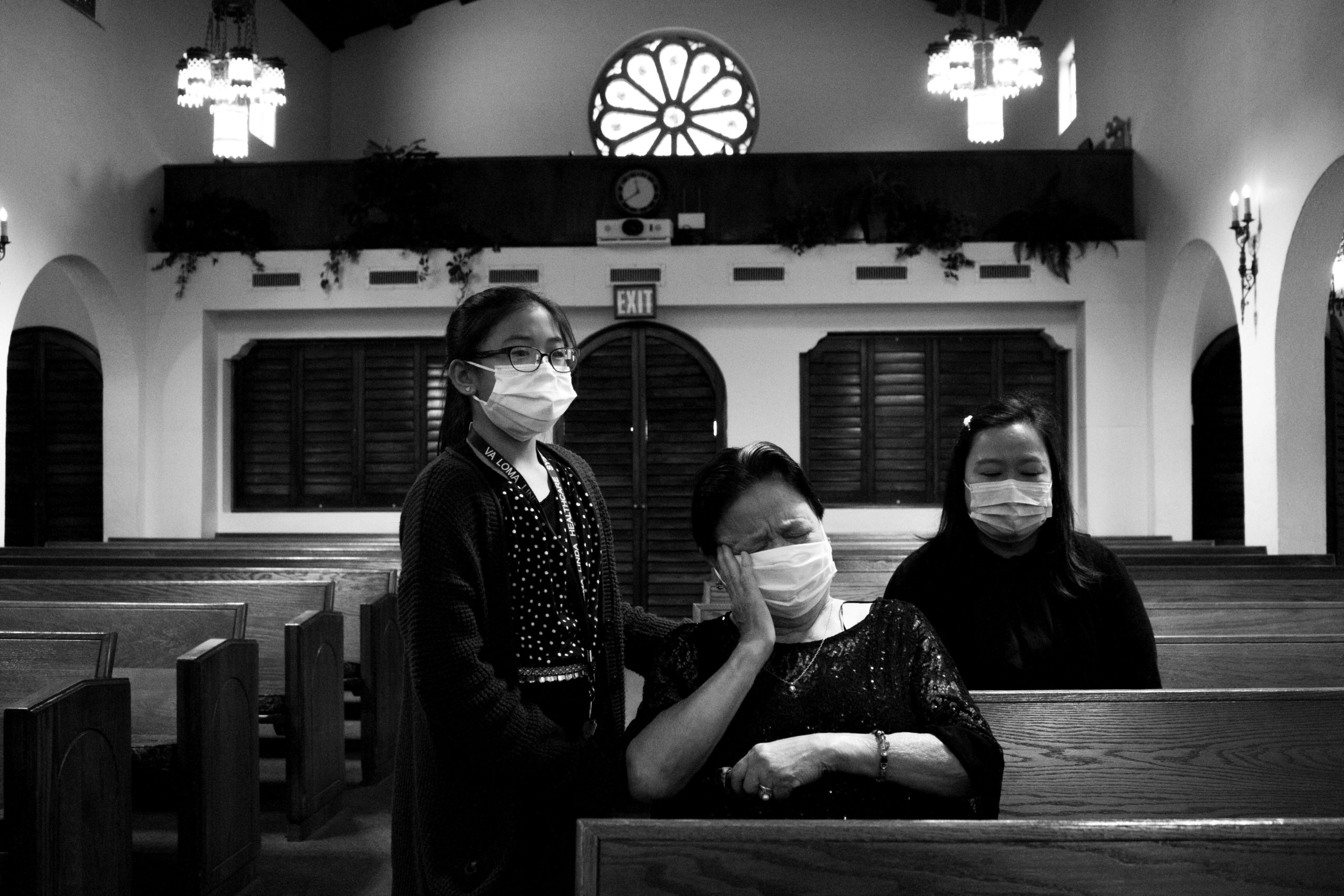 A woman cries while seated in a church, one hand pressing on her face. A young girl comforts her and another woman sits in the row behind them, looking down.