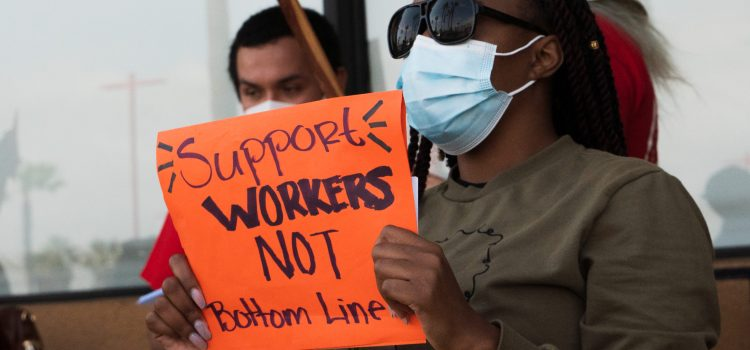 A woman holds an orange sign that says support workers not the bottom line.