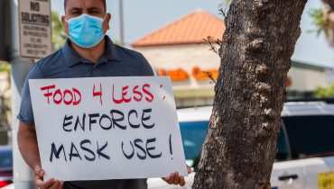 """A man with a mask over his mouth poses in front of a tree and holds a sign saying """"Food 4 Less enforce mask use."""""""