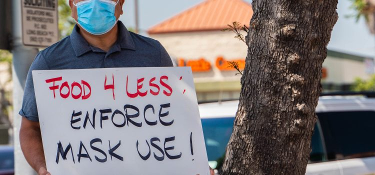 "A man with a mask over his mouth poses in front of a tree and holds a sign saying ""Food 4 Less enforce mask use."""