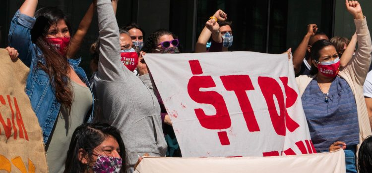 People stand side-by-side, holding up signs and their fists as they pose for a picture.