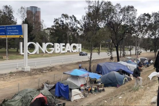 Tents are lined up on the ground in a ditch next to a street in front of sign welcoming people to Long Beach.