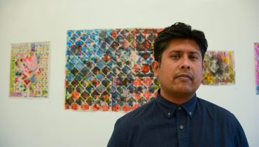 Jose Loza stands in front of three of his art pieces that are posted on a wall.