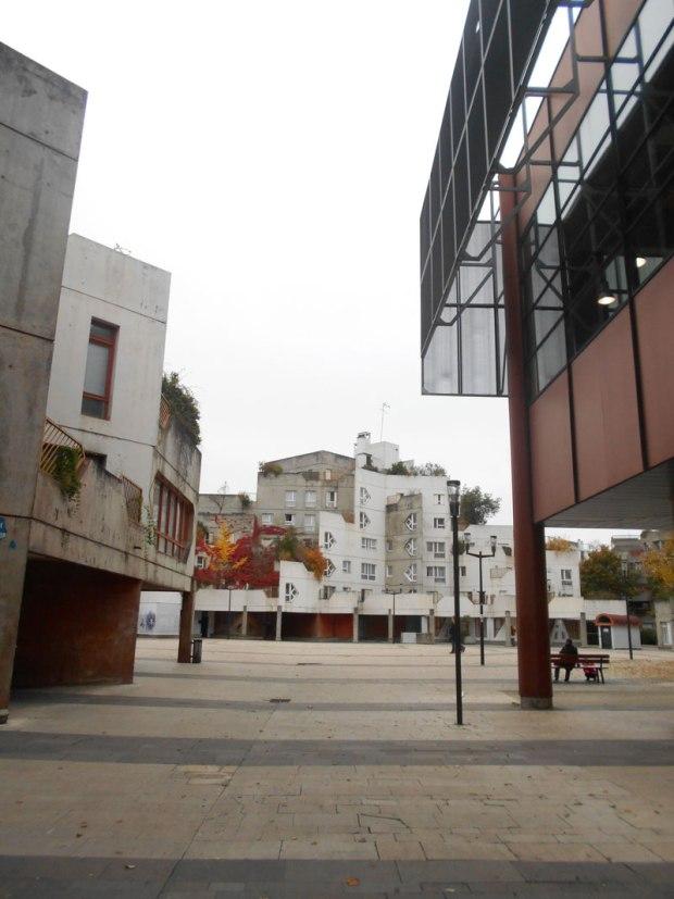 Vue sur la place Voltaire avec la médiathèque à droite qui reprend les couleurs minérales de la place