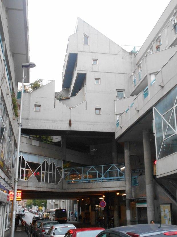 Le dédale de promenées commerciales surplombe la rue; au dessus, les logements se superposent en surplomb les uns des autres pour créer des loggias