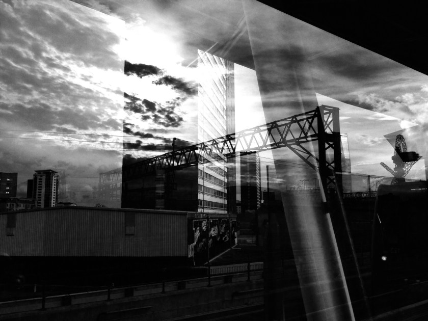 Part of Stratford is reflected in a train window. (© Tilley Harris)
