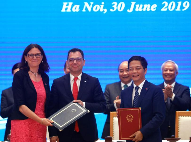 European Commissioner for Trade Cecilia Malmstrom, Romania's Business, Trade and Enterpreneurship Minister Stefan Radu Oprea and Vietnam's Industry and Trade Minister Tran Tuan Anh exchange documents while attending the signing ceremony of EU-Vietnam Free Trade Agreement at the Government Office in Hanoi, Vietnam June 30, 2019. REUTERS/Kham