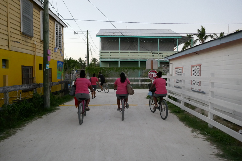 three ladies in pink cycle on Caye Caulker, Belize