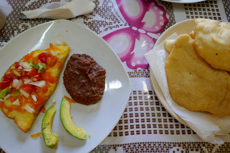Lovely Belizean breakfast of omelette with vegetables, refried beans, avocado slices and fry jacks.