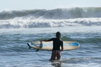 Anete with a surf board in the waves of San Blas near El Tunco.