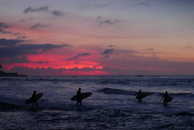 Surfers walking out of the sea at dusk in El Tunco, El Salvador.