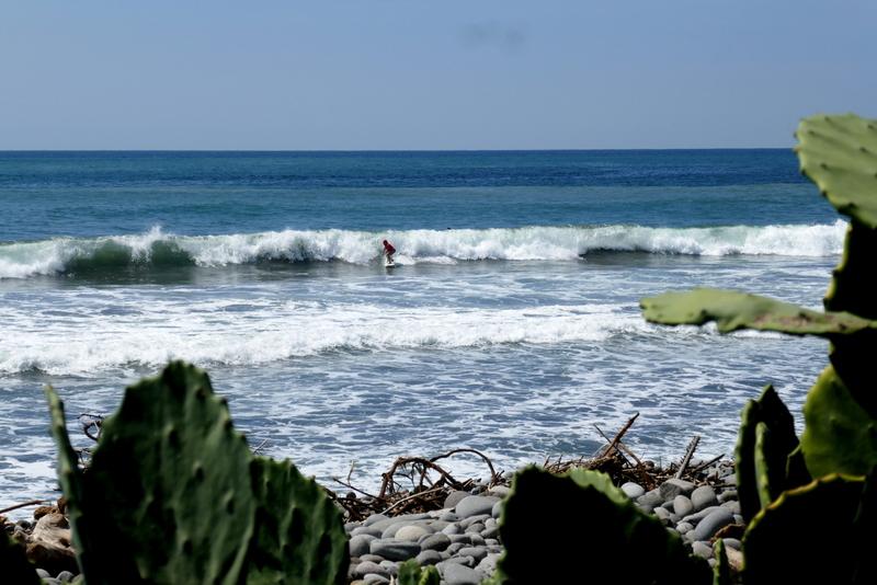 A surfer rides the waves in El Tunco, El Salvador.