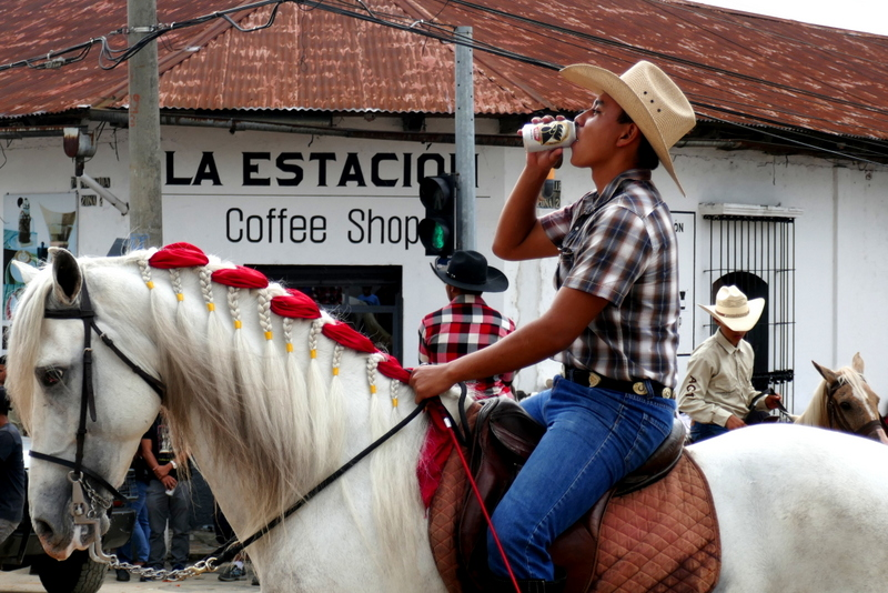 Guatemalan cowboy drinks Gallo on a horse in Cobán.