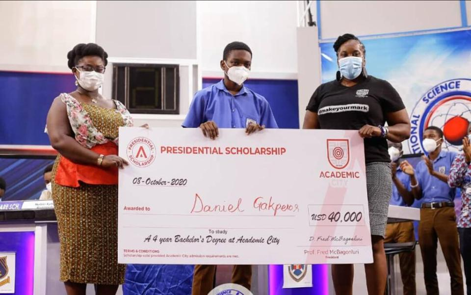 Master Gakpetor, (M) receiving the scholarship  from officials of Academic City College