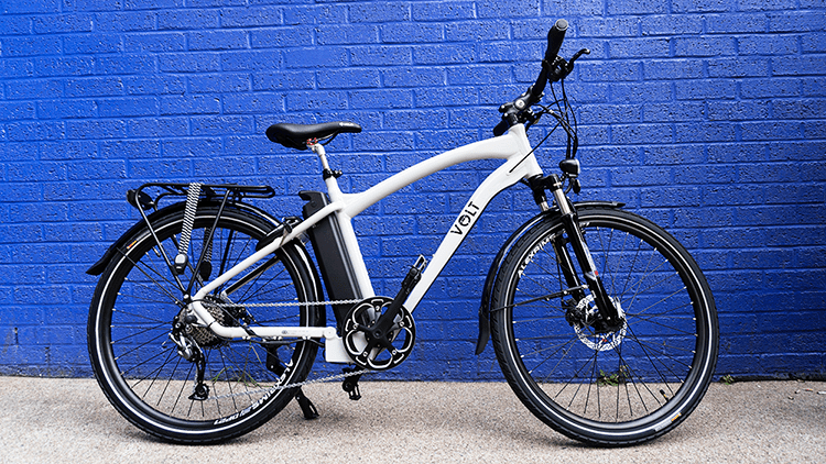The VOLT Pulse light grey e-bike against a blue brick wall