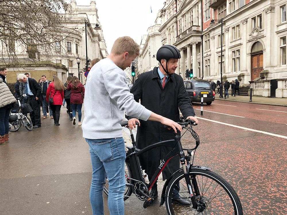 A VOLT Bikes representative shows a member of Parliament an electric bike