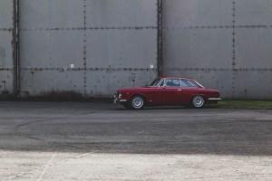Red Alfa Romeo outside aircraft hanger