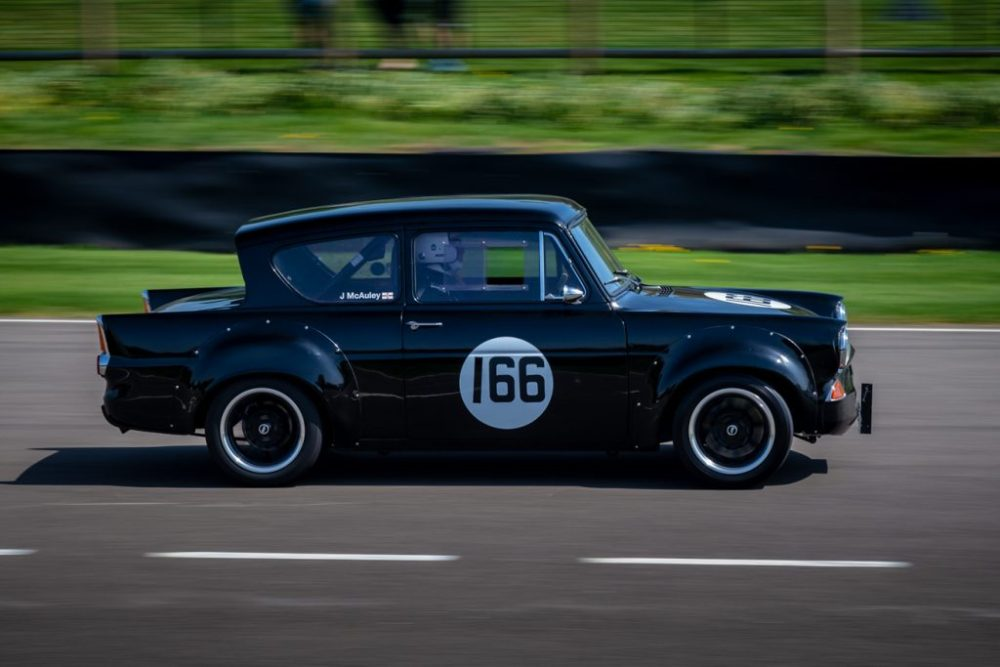 Black Ford Anglia race car speeding along Goodwood motor circuit