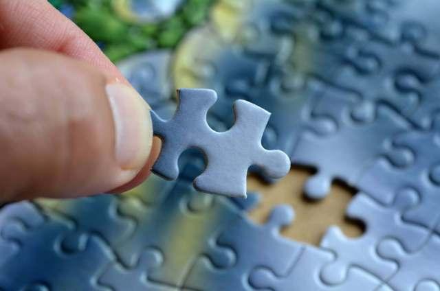 Uma mão coloca a última peça em um quebra.