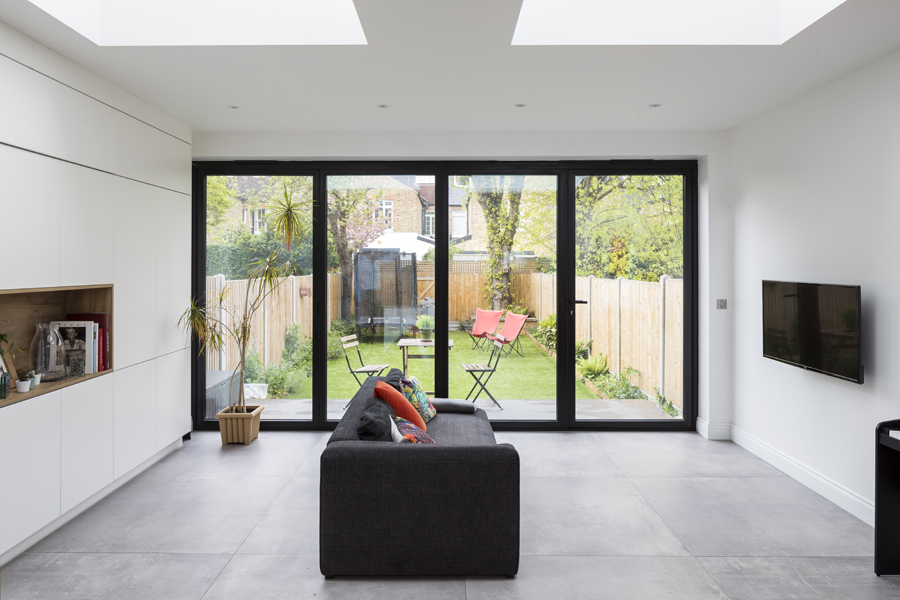 0557 modern living area in extension with grey tiles and white cabinets in london