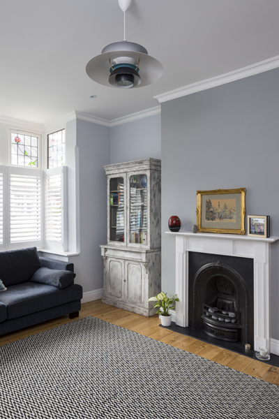 0557 living room with grey walls pattern rug iron fireplace and shutters in london