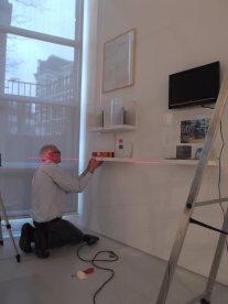 Vakkundig en precies wordt alles opgehangen door een vrijwilliger van het museum