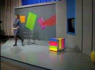 Een draaiend reclamebord doet dienst als decor en chroma-key wand. Jeugdjournaal 1988. ©NOS