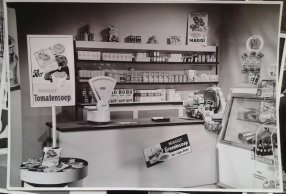 Interieur kruidenierswinkel, mogelijk reclamefilm voor Maggi. Collectie erven Van Baarle