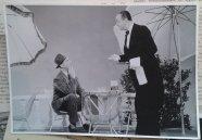 Man alleen op terras met ober voor onbekende reclamefilm. Collectie erven Van Baarle