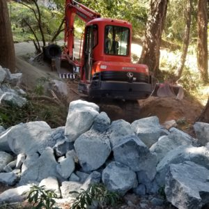 Rock delivery for tank retaining wall system
