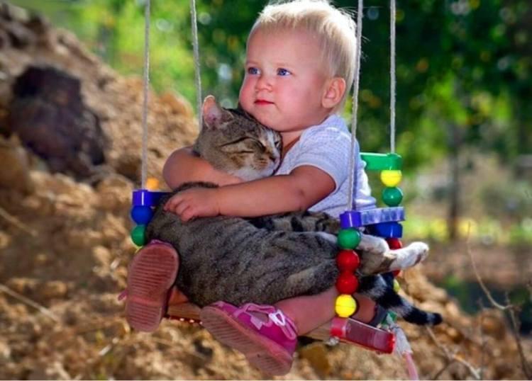 Ребонок обнимает кота