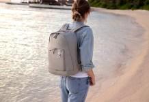 Mulher a usar uma mochila da samsonite numa praia