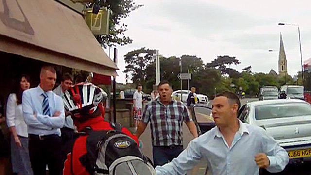 A car passenger punching a cyclist