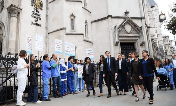 Doctors from Justice for Health walk past supporters outside the Royal Courts of Justice [Image: Leon Neal/Getty Images].