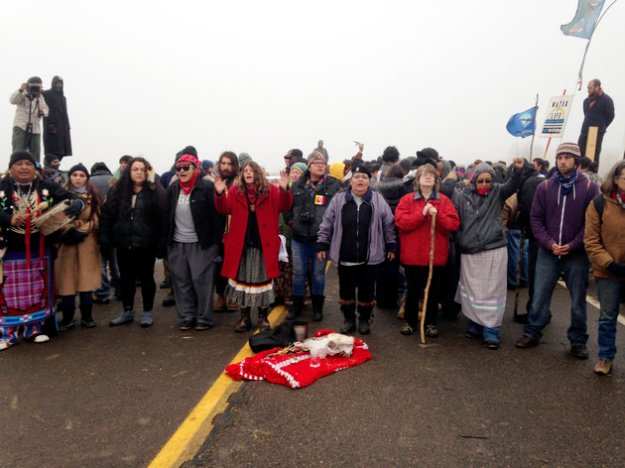 """Protesters fighting construction on the Dakota Access Pipeline block a highway near Cannon Ball, North Dakota, on October 26. Facebook users are """"checking in"""" at Standing Rock Indian Reservation in solidarity [Image: James MacPherson/AP]."""