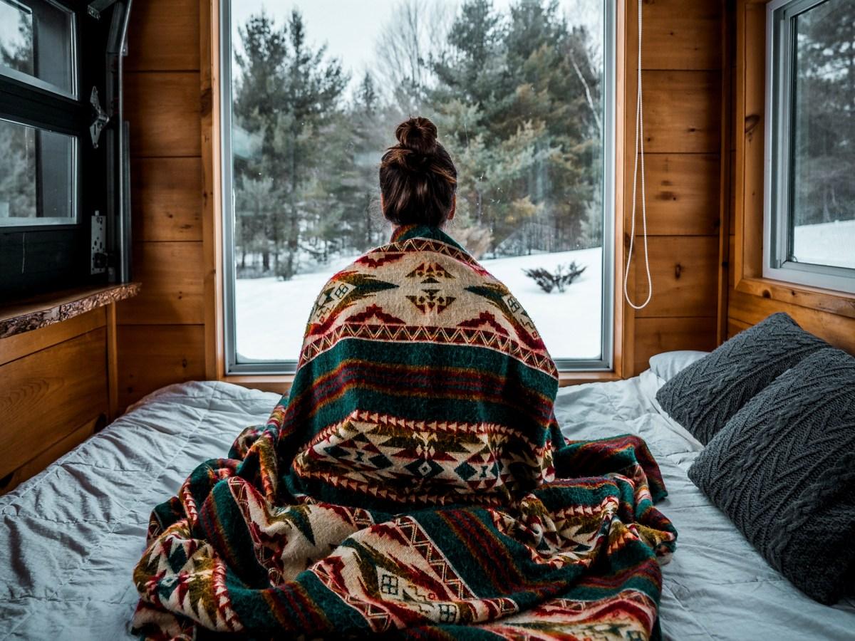 Femme regardant par la fenêtre une forêt recouverte de neige.