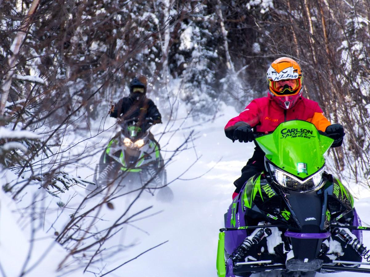 Deux personnes faisant de la motoneige dans la forêt.