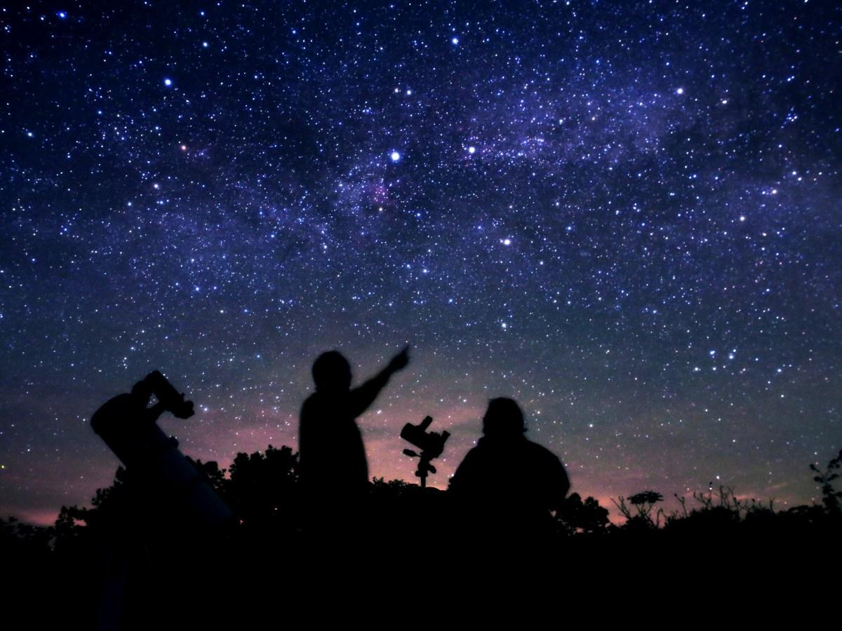 Silhouette de deux personnes admirant le ciel étoilé.