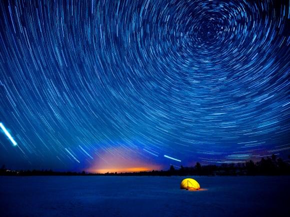Éblouissant ciel étoilé qui scintille au-dessus d'une tente isolée en hiver.