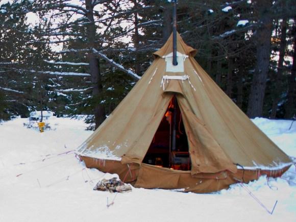 Tente en canevas érigée dans la neige