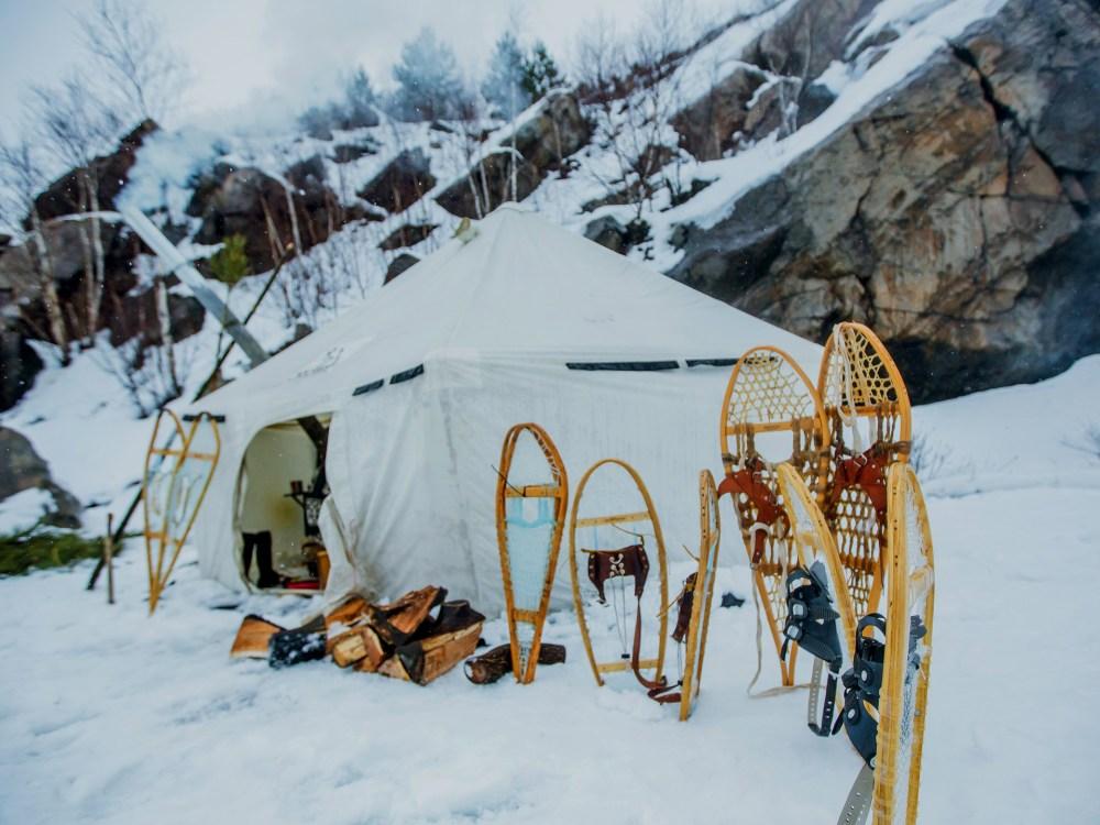 Tente de camping d'hiver avec raquettes plantées dans la neige à l'extérieur
