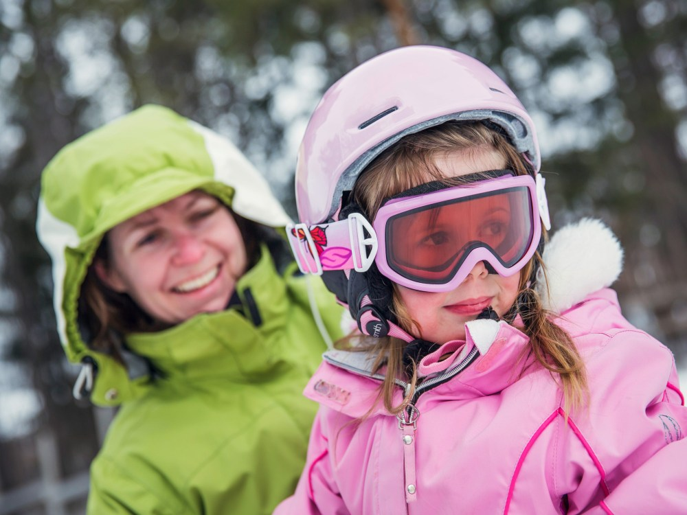Une mère et sa fille sur une pente de ski