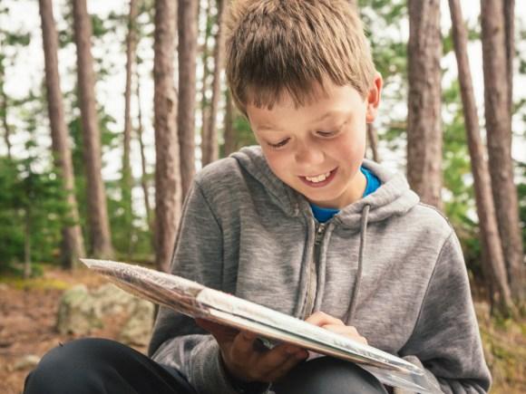Jeune garçon lisant les directives pour une expérience amusante.