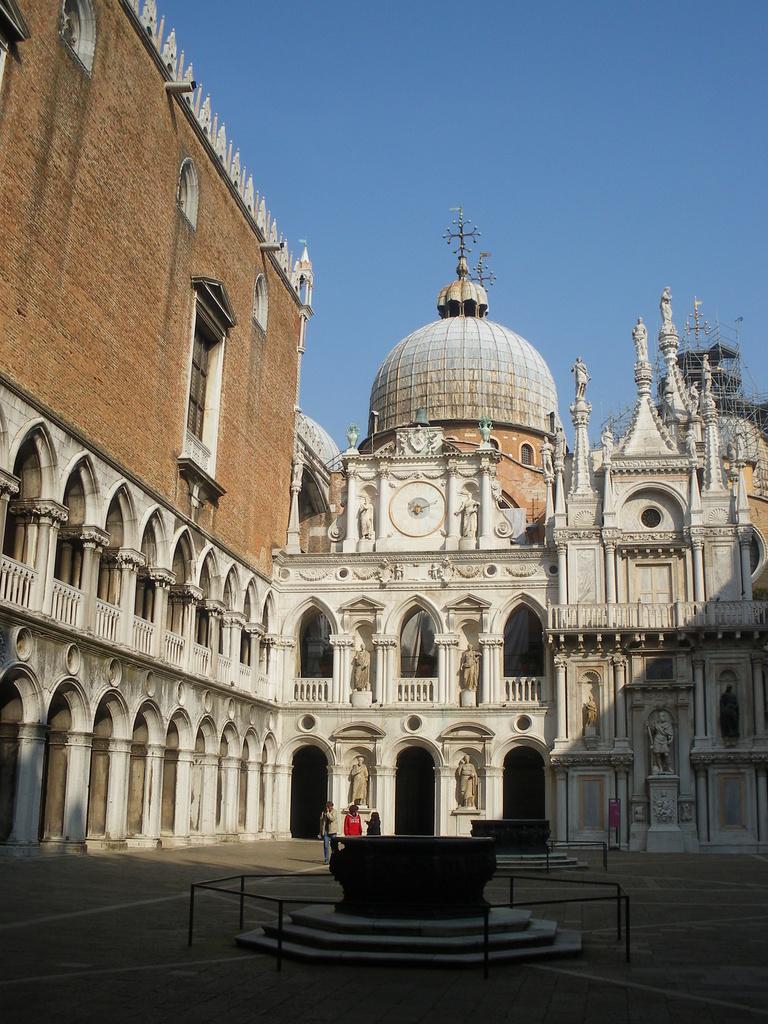 Cour intérieure du Palais qui doit sa beauté aux margelles des puits (XVIème siècle). Derrière,la façade dite de l'horloge et ses 6 statues romaines.